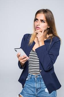 Ritratto di una donna pensierosa utilizzando il telefono cellulare isolato