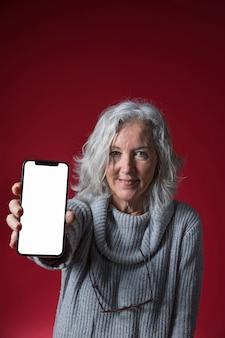Ritratto di una donna senior che mostra telefono cellulare con display bianco bianco