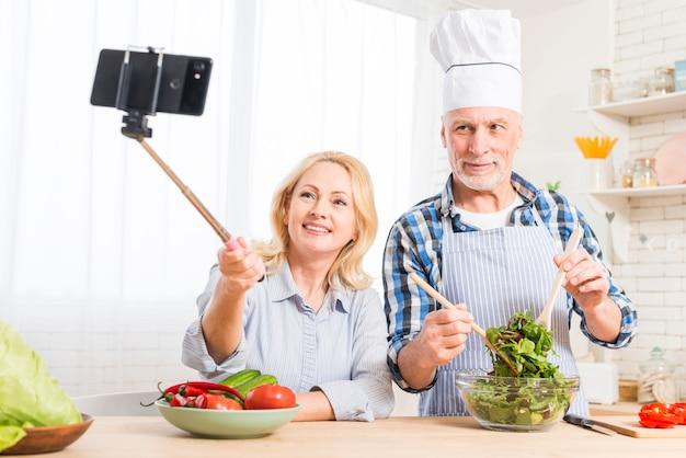 Ritratto di una donna senior che prende selfie sul telefono cellulare con il suo marito che prepara l'insalata nella cucina