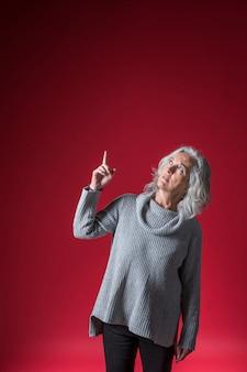 Ritratto di una donna senior che punta il dito verso l'alto su sfondo rosso brillante