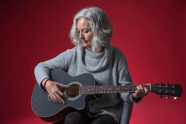 Ritratto di una donna senior che si siede sulla sedia che gioca la chitarra contro fondo rosso