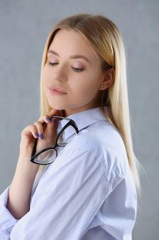 Ritratto di una donna sexy in camicia da uomo con gli occhiali