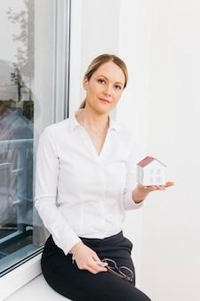Ritratto di una donna sicura che si siede sulla guarnizione della finestra che tiene il modello della casetta