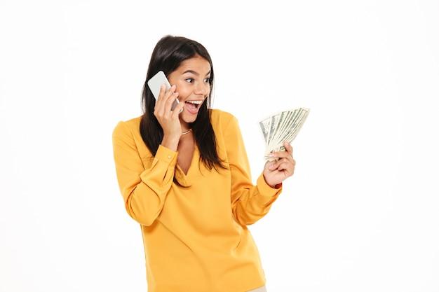 Ritratto di una donna sorpresa allegra che parla sul telefono cellulare