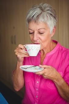 Ritratto di una donna sorridente che beve un tè
