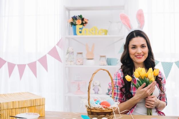 Ritratto di una donna sorridente che indossa orecchie da coniglio tenendo in mano i tulipani