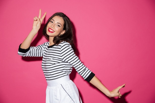 Ritratto di una donna sorridente che mostra gesto di pace