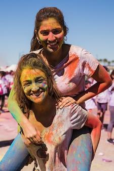 Ritratto di una donna sorridente che porta la sua amica sul retro celebrando il festival di holi