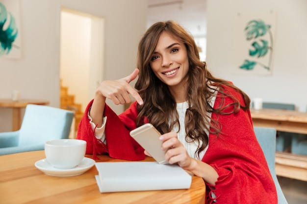 Ritratto di una donna sorridente che punta il dito al telefono cellulare
