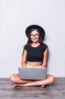 Ritratto di una donna sorridente che si siede sul pavimento con il computer portatile isolato su fondo grigio