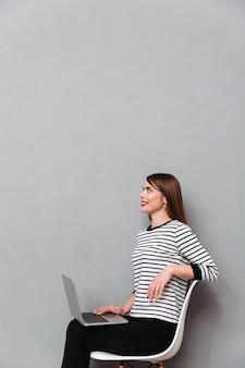 Ritratto di una donna sorridente che si siede sulla sedia con il computer portatile