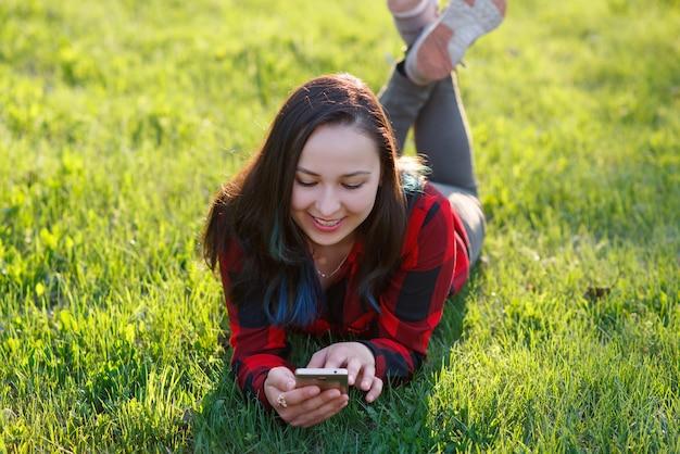 Ritratto di una donna sorridente che si trova sull'erba verde e che per mezzo dello smartphone all'aperto