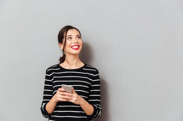 Ritratto di una donna sorridente che tiene telefono cellulare