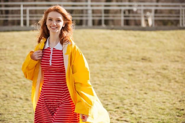 Ritratto di una donna sorridente dei capelli rossi nella camminata del cappotto