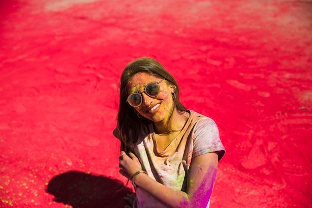 Ritratto di una donna sorridente in piedi sulla polvere di colore rosso holi