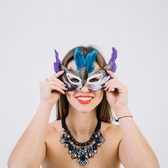 Ritratto di una donna sorridente in topless che indossa la maschera di piume su sfondo bianco