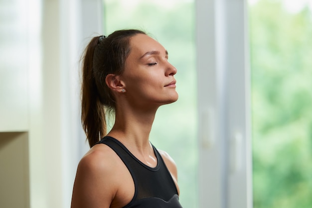 Ritratto di una donna sportiva che fa le esercitazioni a casa