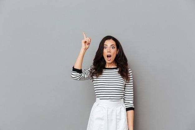 Ritratto di una donna stupita che punta il dito