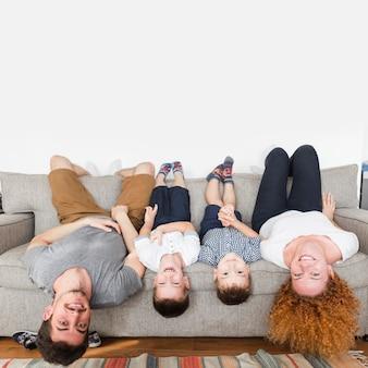 Ritratto di una famiglia felice sdraiato a testa in giù sul divano