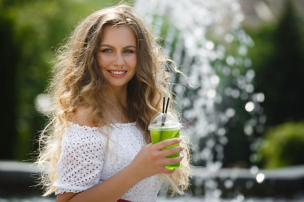 Ritratto di una giovane bella donna attraente all'aperto in estate con un bicchiere di succo o bevanda ghiacciata. ragazza graziosa fuori con il mojito fresco