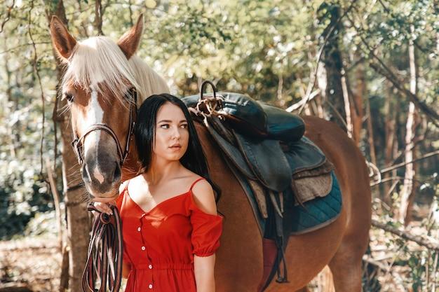 Ritratto di una giovane bella donna castana che tiene un cavallo per la briglia