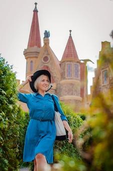 Ritratto di una giovane bella donna felice alla moda in posa in strada