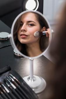 Ritratto di una giovane bruna applicando cosmetici
