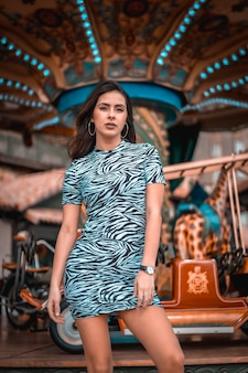 Ritratto di una giovane bruna seduta in abito stretto su una giostra in fiera, guardando a destra