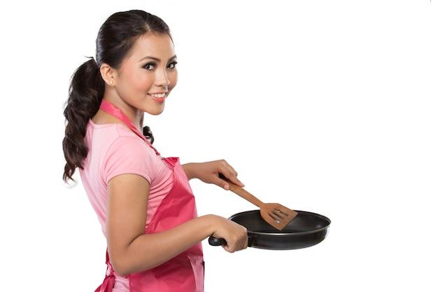 Ritratto di una giovane casalinga pronta a cucinare