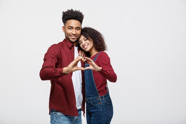 Ritratto di una giovane coppia africana sorridente vestita in abbracciare e mostrando il gesto del cuore