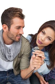 Ritratto di una giovane coppia che canta nel microfono