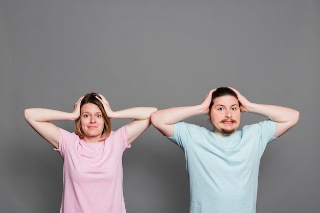 Ritratto di una giovane coppia con le sue mani sulla testa avendo mal di testa