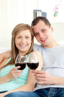 Ritratto di una giovane coppia felice che beve vino rosso