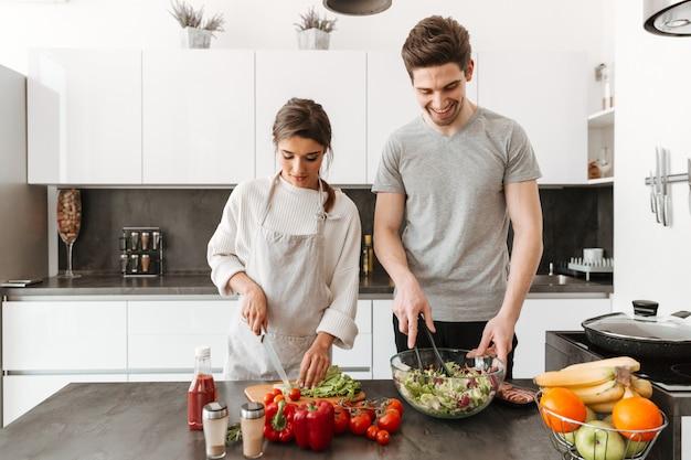 Ritratto di una giovane coppia felice che cucina insalata