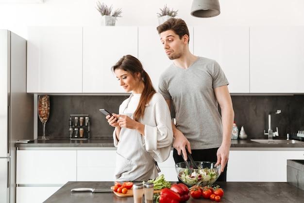 Ritratto di una giovane coppia sorridente che cucina insieme