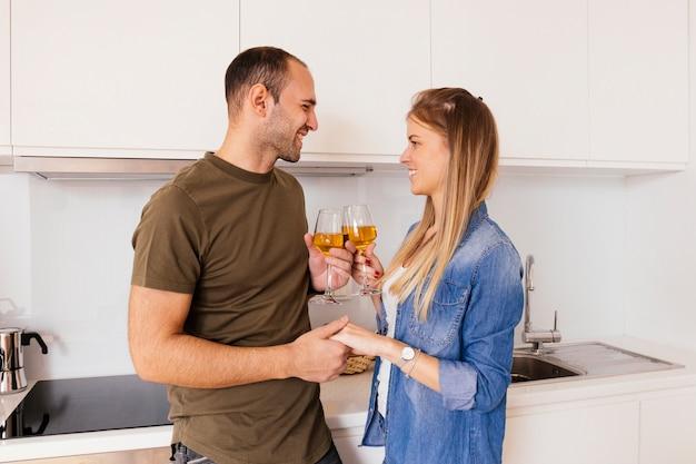 Ritratto di una giovane coppia sorridente che tiene la mano di ciascuno che tosta i bicchieri di vino nella cucina