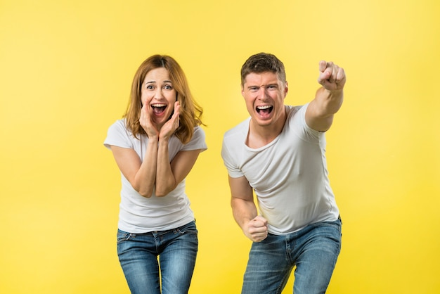 Ritratto di una giovane coppia urlando e tifo con gioia contro sfondo giallo