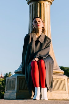 Ritratto di una giovane donna alla moda in piedi sotto il pilastro guardando la fotocamera