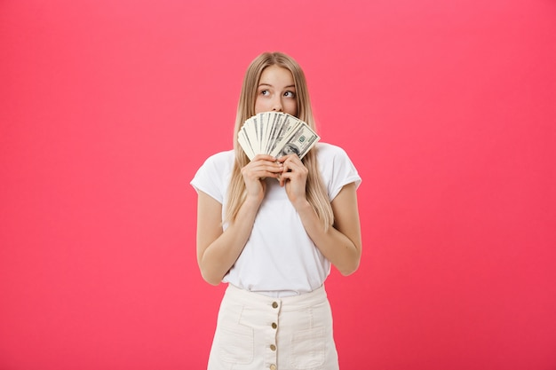Ritratto di una giovane donna allegra che tiene denaro banconote e celebrando isolato su sfondo rosa