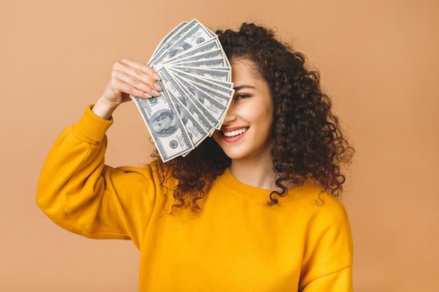 Ritratto di una giovane donna allegra che tiene le banconote e la celebrazione dei soldi isolate sopra fondo beige.