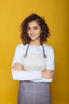 Ritratto di una giovane donna amichevole con il grembiule