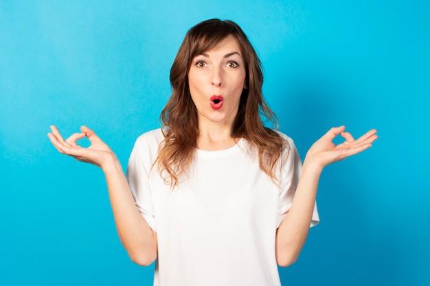 Ritratto di una giovane donna amichevole in maglietta casual con un gesto di meditazione e una faccia sorpresa sul blu, relax