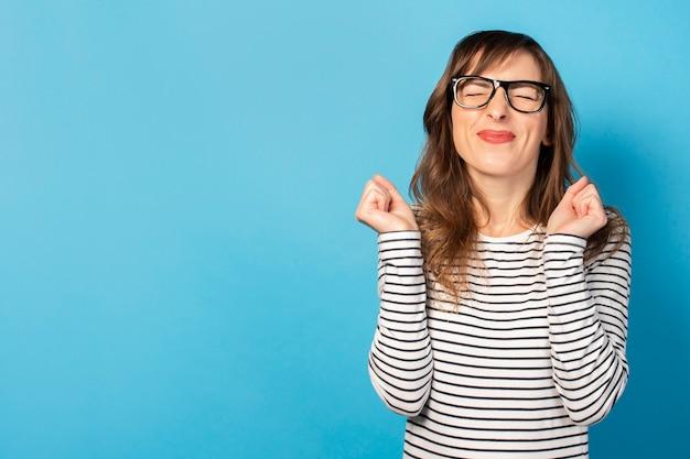 Ritratto di una giovane donna amichevole in maglietta casual e occhiali molto emotivamente felice per qualcosa sul blu. volto emotivo. gesto di festa