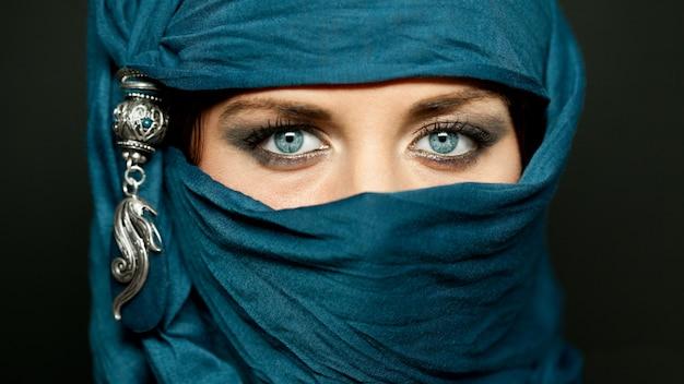 Ritratto di una giovane donna araba con i suoi bellissimi occhi azzurri nel tradizionale niqab di stoffa islamica