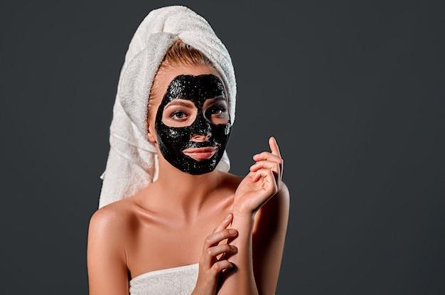 Ritratto di una giovane donna attraente con un asciugamano sulla testa con una maschera nera detergente sul viso su un muro grigio.