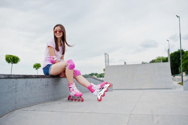 Ritratto di una giovane donna attraente in pantaloncini, maglietta, occhiali da sole e pattini seduto sulla panchina di cemento nella pista di pattinaggio all'aperto.