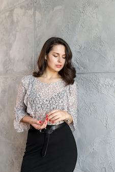 Ritratto di una giovane donna attraente in piedi contro il muro di cemento grigio