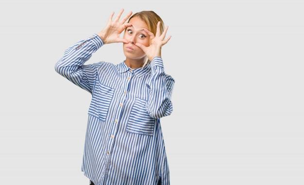 Ritratto di una giovane donna bella bionda sorpreso e scioccato, guardando con gli occhi spalancati