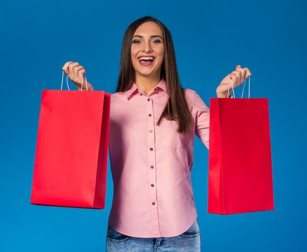 Ritratto di una giovane donna bellissima con borse per lo shopping.