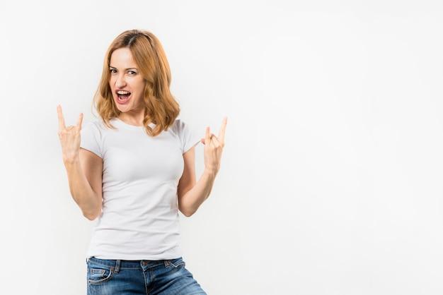 Ritratto di una giovane donna bionda che mostra gesto di rock-and-roll contro il contesto bianco